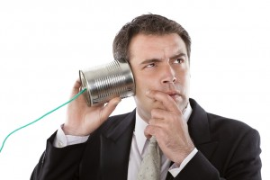 Businessman listening to a conversation from a telephone can